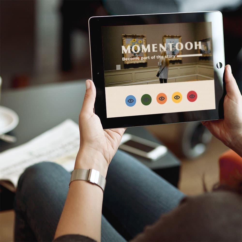 Woman holding a tablet with the image of the Momentooh brand identity